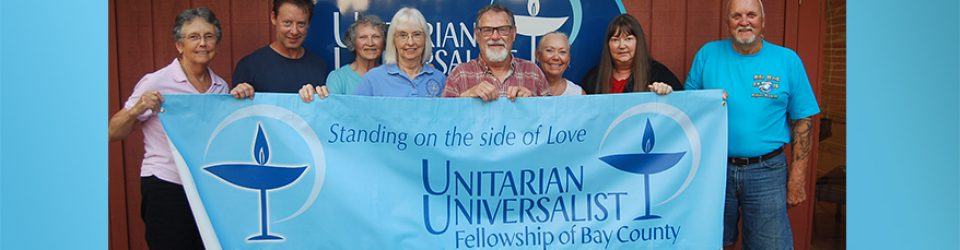 Unitarian Universalist Fellowship of Bay County Social Justice team unfurls new banner.